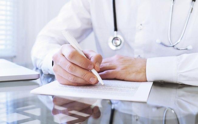 Doctor escribiendo una recomendación para Asesoría Médica Integral (AMI) por el resultado del pago de sus honorarios médicos y con acción de recomendación